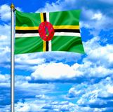 Dominica waving flag against blue sky royalty free stock photography