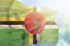 Dominica waving flag against blue sky with sunrays stock photography