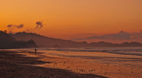 Dominical Sunrise. First surfer out with a beautiful sunrise at Playa Dominical, Costa Rica Stock Image