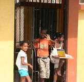 Dominican Children. Shows the culture of the Dominican Republic. Children standing in doorways waving at people passing by is a common scene. One little girl is Royalty Free Stock Images