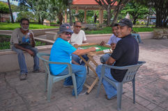 Dominican Dominos. Four men playing dominos in the town square in Cabrera, Dominican Republic while another man looks on Stock Photography