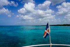 Dominican flag over the ocean Stock Photography