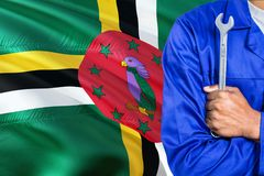 Dominican Mechanic in blue uniform is holding wrench against waving Dominica flag background. Crossed arms technician.  royalty free stock photography