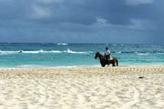 Dominican policeman on a black horse patrols the beach area. stock images