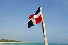 Dominican Republic. National flag of the Dominican Republic, placed in plina tropical bavaro beach, Punta Cana Royalty Free Stock Photography
