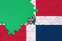 Dominican Republic flag is depicted on a completed jigsaw puzzle with free green copy space on the left side.  stock photo