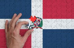 Dominican Republic flag is depicted on a puzzle, which the man`s hand completes to fold.  royalty free stock photo