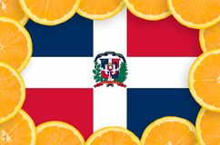 Dominican Republic flag in fresh citrus fruit slices frame. Dominican Republic flag in frame of orange citrus fruit slices. Concept of growing as well as import stock photo