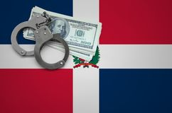 Dominican Republic flag with handcuffs and a bundle of dollars. The concept of breaking the law and thieves crimes.  stock photo