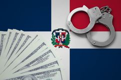 Dominican Republic flag with handcuffs and a bundle of dollars. The concept of illegal banking operations in US currency.  stock images