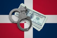 Dominican Republic flag with handcuffs and a bundle of dollars. Currency corruption in the country. Financial crimes.  royalty free stock photography