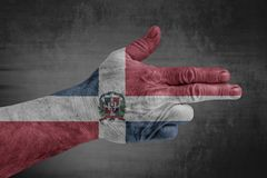 Dominican Republic flag painted on male hand like a gun. On concrete background stock images