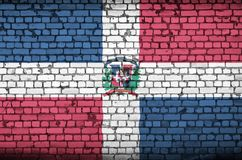 Dominican Republic flag is painted onto an old brick wall royalty free stock photos