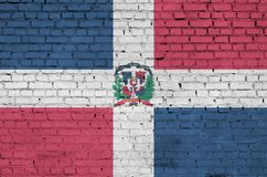 Dominican Republic flag is painted onto an old brick wall royalty free illustration
