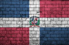 Dominican Republic flag is painted onto an old brick wall stock image