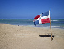 Dominican republic. Flag planted in the sand of punta cana beach Royalty Free Stock Photo
