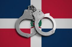 Dominican Republic flag and police handcuffs. The concept of observance of the law in the country and protection from crime.  royalty free stock photos