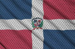 Dominican Republic flag printed on a polyester nylon sportswear. Mesh fabric with some folds stock photos