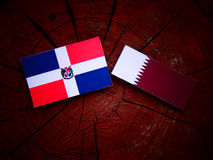 Dominican Republic flag with Qatari flag on a tree stump isolated. Dominican Republic flag with Qatari flag on a tree stump Royalty Free Stock Photo