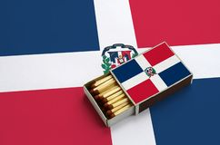 Dominican Republic flag is shown in an open matchbox, which is filled with matches and lies on a large flag.  royalty free stock photos