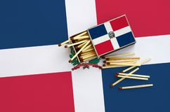 Dominican Republic flag is shown on an open matchbox, from which several matches fall and lies on a large flag.  stock photos