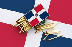 Dominican Republic flag is shown on an open matchbox, from which several matches fall and lies on a large flag.  royalty free stock images