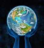 Dominikanska republiken på planetjord i händer Royaltyfri Bild