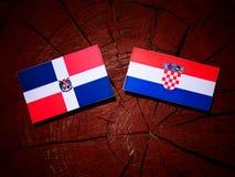 Dominikanska republikenflagga med den kroatiska flaggan på en isola för trädstubbe Royaltyfri Fotografi