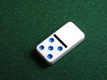 Domino. Single white domine on green background Stock Images