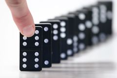 Domino. Finger ready to push over dominoes Stock Photos