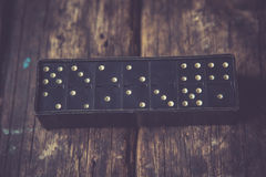 Domino. Black Domino on a old wooden background Stock Photos