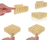Domino in a creamy color arranged in a row pressed by a finger b. Egins to overturn. The blocks are arranged in front of an empty part. Composition on a white Royalty Free Stock Photo