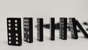 Domino effect, black wooden domino line curve stock video footage
