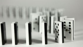 Domino effect. Domino falling down in chain reaction