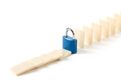 Domino and Lock. Concept of business damage control Stock Photos