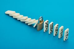 Domino and lock. In A Row Over Blue Background Royalty Free Stock Images