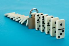 Domino and lock. In A Row Over Blue Background Stock Photography