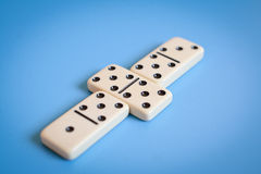 Domino parts, only showing number five over blue table Stock Images