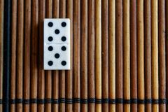 Domino piece on the bamboo brown wooden table background. Domino set - five - 5 dots. Domino piece on the bamboo brown wooden table background. Domino set stock photo