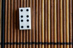 Domino piece on the bamboo brown wooden table background. Domino set - four - 4 dots. Royalty Free Stock Images