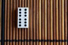 Domino piece on the bamboo brown wooden table background. Domino set - six - 6 dots. Royalty Free Stock Photo