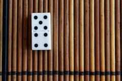 Domino piece on the bamboo brown wooden table background. Domino set - four - 5 dots. Stock Photography