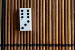 Domino piece on the bamboo brown wooden table background. Domino set - three - 6 dots. Royalty Free Stock Images
