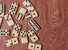 Domino pieces on the brown wooden table background.  Stock Image