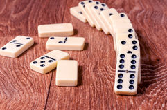 Domino pieces on the brown wooden table background.  Royalty Free Stock Image