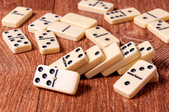 Domino pieces on the brown wooden table background.  Stock Photo