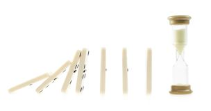 Domino pieces falling on to the sandglass Royalty Free Stock Photos