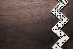 Domino pieces forming zigzag over wooden table. Domino pieces forming zigzag on wooden table royalty free stock photo