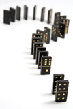 The Domino Question. Black and gold dominoes arranged in a question mark. Isolated on a white background with a narrow depth of field Royalty Free Stock Photography