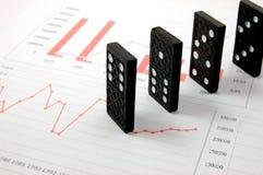 Domino rischioso sopra un diagramma finanziario di affari Fotografie Stock Libere da Diritti